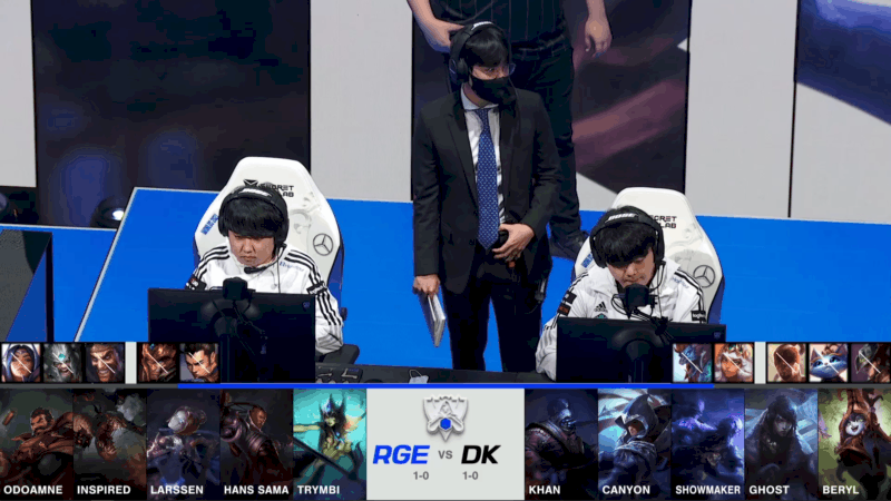A screenshot from the 2021 World Championship Main Event Group Stage broadcast, showing the champion drafts between Rogue and DAMWON KIA with a shot of two DAMWON players and their coach on stage above.
