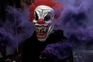 Creepy clown mask with purple smoke