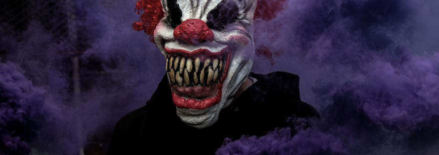 Creepy clown mask with purple smoke