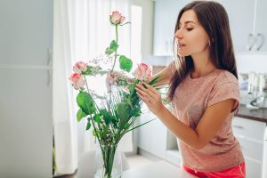 Woman puts roses in vase. Housewife taking care of coziness on kitchen decorating with flowers.