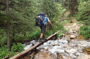 David on crossing creek on a log