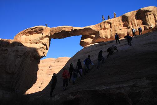 climbing the a natural bridge in the wadi rum desert