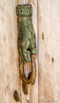 Open hand doorknocker signifies the residence of a religious woman