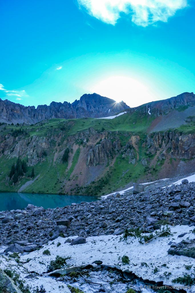 blue lake with sun coming over ridge