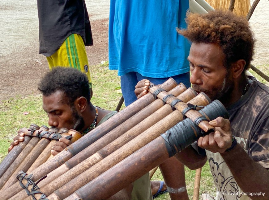 islanders blowing in pipes to make music