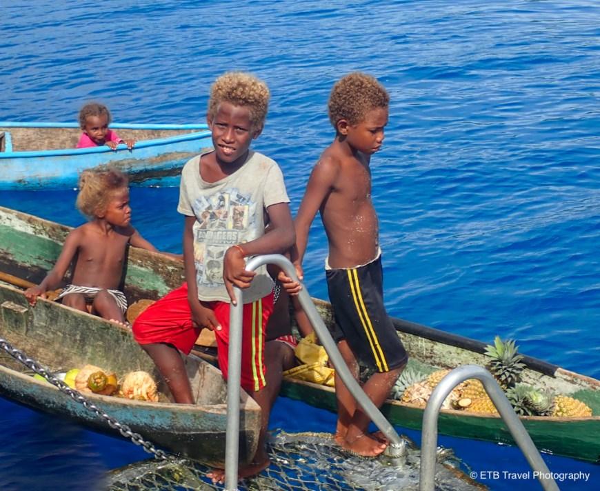 solomon kids selling us fruit on the taka