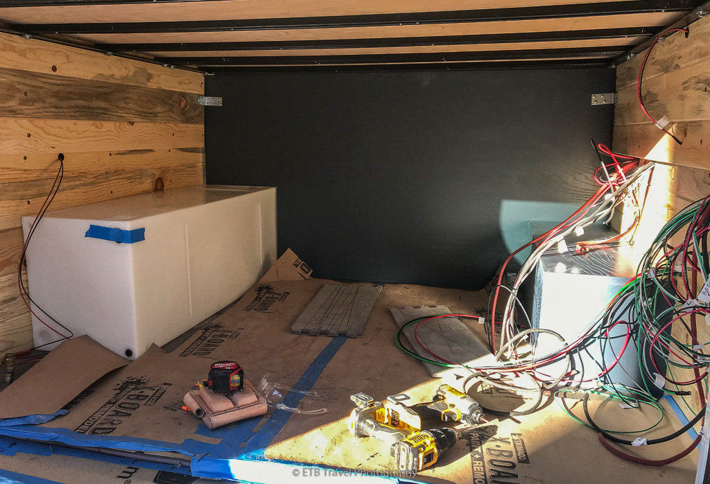 water tank and battery compartment under bed in camper conversion