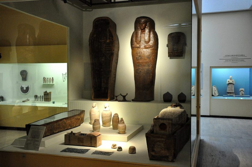 Grave finds from ancient Egypt. In this grave, we can see coffins, mummies, canopic jars, head part of a wooden coffin, baskets for beads, wooden chest for ushabties, and beadwork covers.