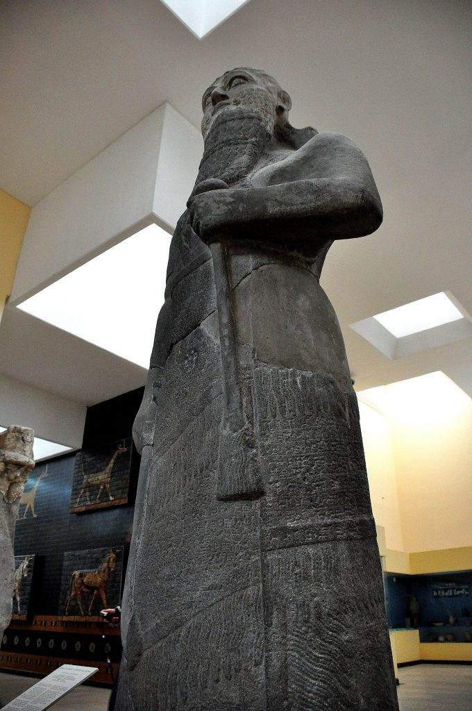 Basalt statue of Shalmaneser III, king of Assyria from 858-824 BCE. The cuneiform inscriptions on the statue narrates a brief account of the king's genealogical titles and characteristics. The inscriptions also say that the king's military campaigns against the lands of Urartu, Syria, Namri, Que, and Table have come to an end. On the background, a sirrush and an auroch from Babylon appear.