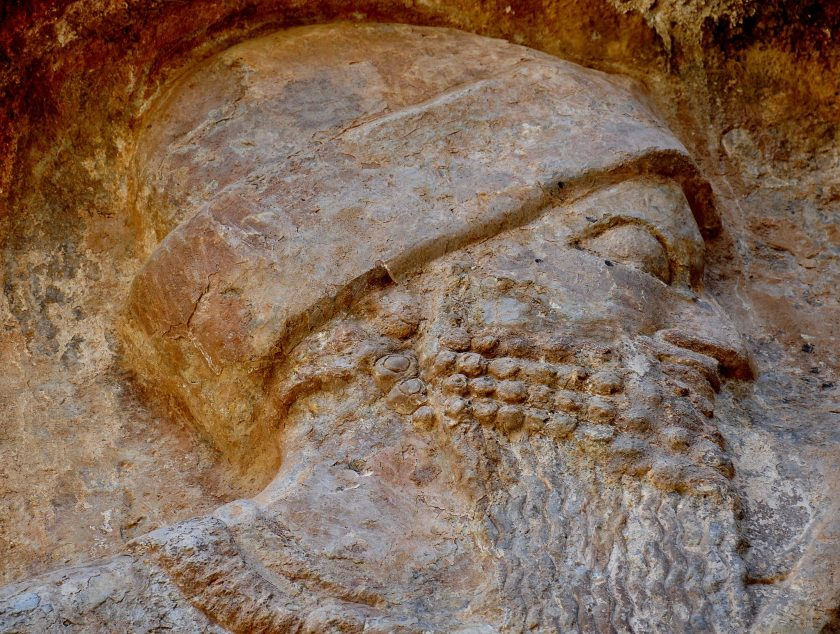 A close-up view of the head of the main figure of the relief. Note the rolled up cap which fits the head as well as the curly beard.