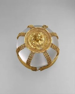 ​Hairnet with Medallion, ca. 200–150 BCE. The luxurious nature of this gold hairnet, or kekryphalos, which would have been owned by a woman of high status, attests to the wealth of the Greek Hellenistic world. A substantial amount of hair would have been required to secure this complex and expensive accessory at the back of the head. It can be compared to the hairnet worn by Arethusa on the Syracusan coin (no. 18). Containment defines the purpose of this gold object, and yet its central medallion shows a maenad (follower of Dionysos, god of wine), who personifies abandon. Even her hair seems to escape the confines of a grape vine wreath. Hairnets of this type have been associated with Ptolemaic Egypt, where the ruling families included queens such as Berenike II (no. 32) and Cleopatra VII, who was famous for her love affairs with Julius Caesar and Mark Antony.