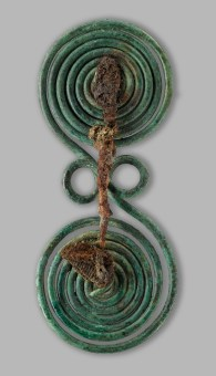 Spectacle-Shaped Brooch with Fabric Remains Early Iron Age (1000–700 BC). Copper alloy, iron, and textile. L. 5.9 in; Diam. coils 2.4 in, 2.6 in (L. 15 cm; Diam. coils 6 cm, 6.5 cm). From Olympus. Tumulus cemetery of Mesonisi, Tumulus 2, grave D. Archaeological Museum of Dion. Photo © Hellenic Ministry of Culture and Sports, Ephorate of Antiquities of Pieria, and the Dion Excavations. Courtesy Onassis Cultural Center NY.
