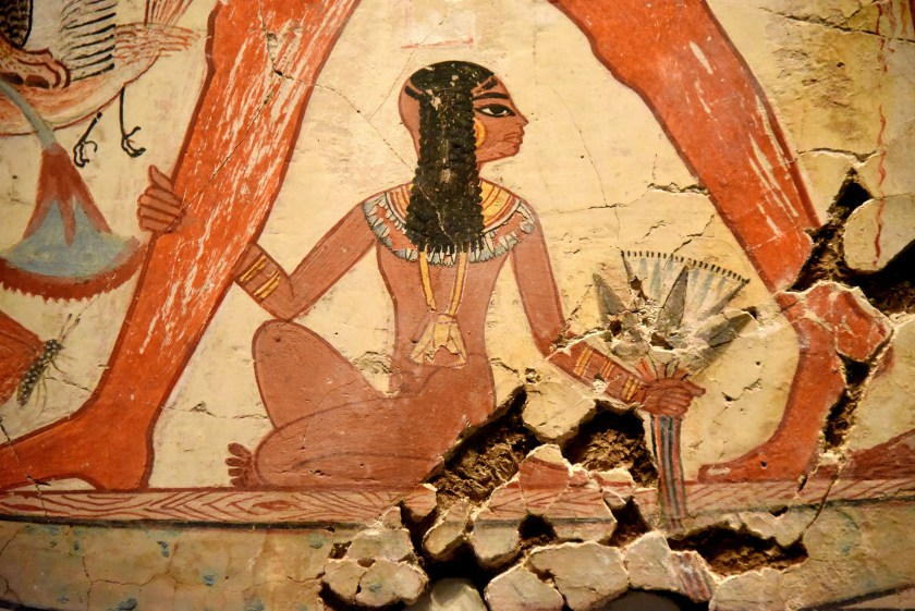 Nebamun's daughter sits on the boat below the figure of her father. She grips her father's right leg with her right hand while her left hand grips a lotus flower. Photo © Osama S. M. Amin.