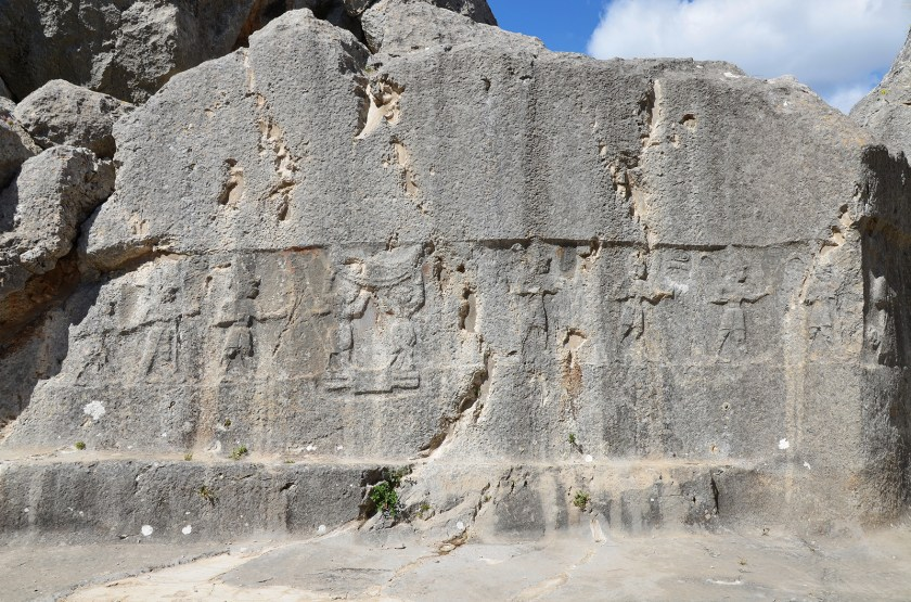 Chamber A, two bull men stand between male Hittite gods on the hieroglyphic symbol of the earth and supporting the sky.