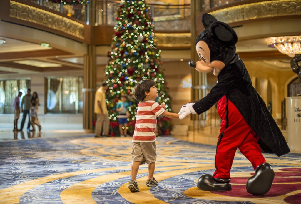 Mickey Mouse and a little boy in front of Christmas tree.