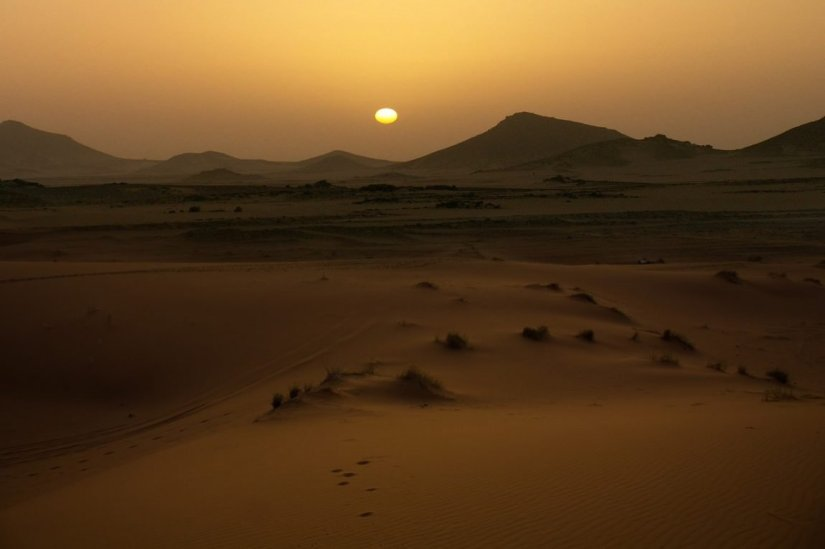 A sunset happening in the Sahara desert with an orange-toned sky.