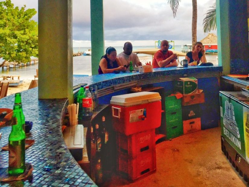 a colorful bar area with a mosaic tile counter and people sitting at the bar with the beach in the distance