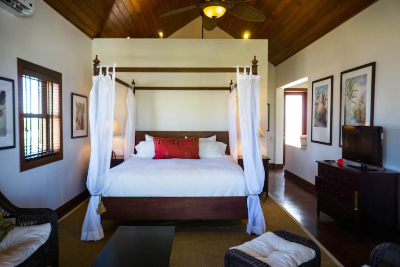 a fancy suite with a four poster bed, high ceilings and flat screen tv