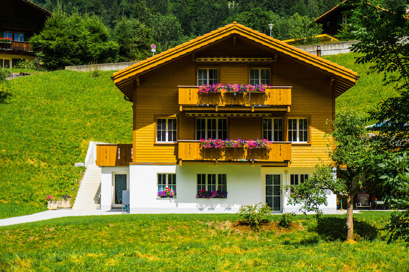 A traditional Swiss wooden chalet style house with colorful flowers in the planterboxes in the small town of Lauterbrunnen, a great day trip from Interlaken