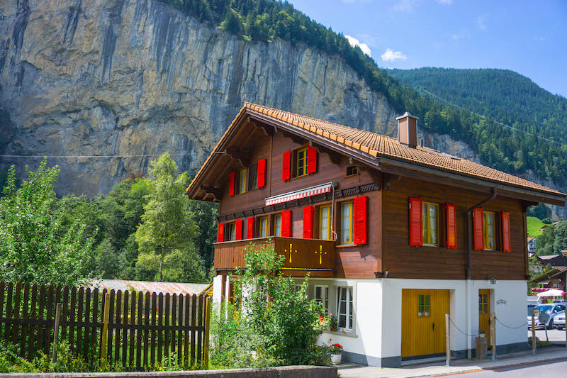 [brown house with red shutters in a valley] Lauterbrunnen is one of the most scenic places in Switzerland