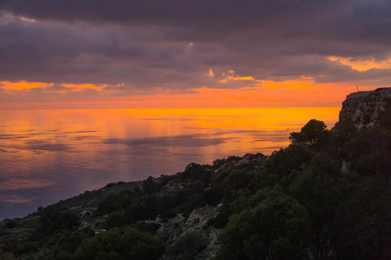 Photo of a sunset in Malta at Dingli cliffs with orange and purple tones