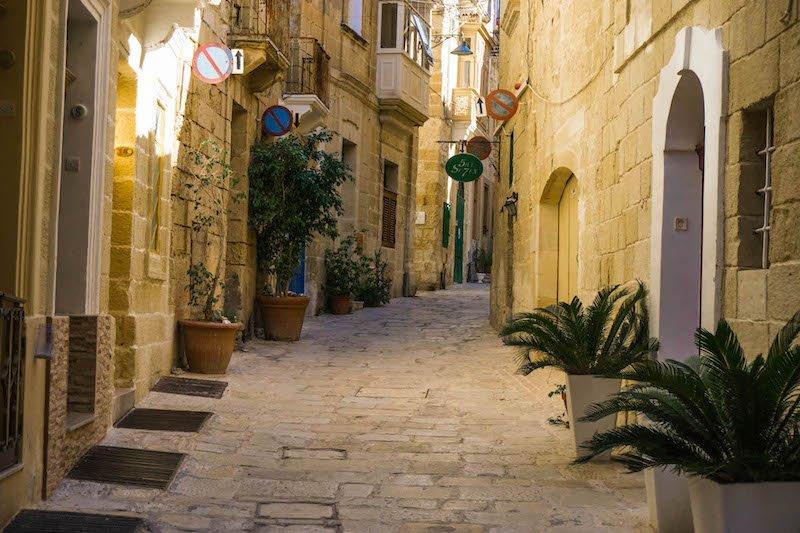 A sandstone-brick street in Malta's Birgu with colorful balconies and doorways