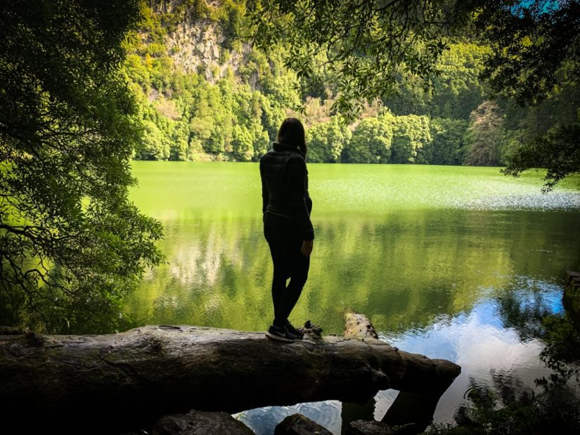 allison standing on a log looking at the green lake lagoa de congro