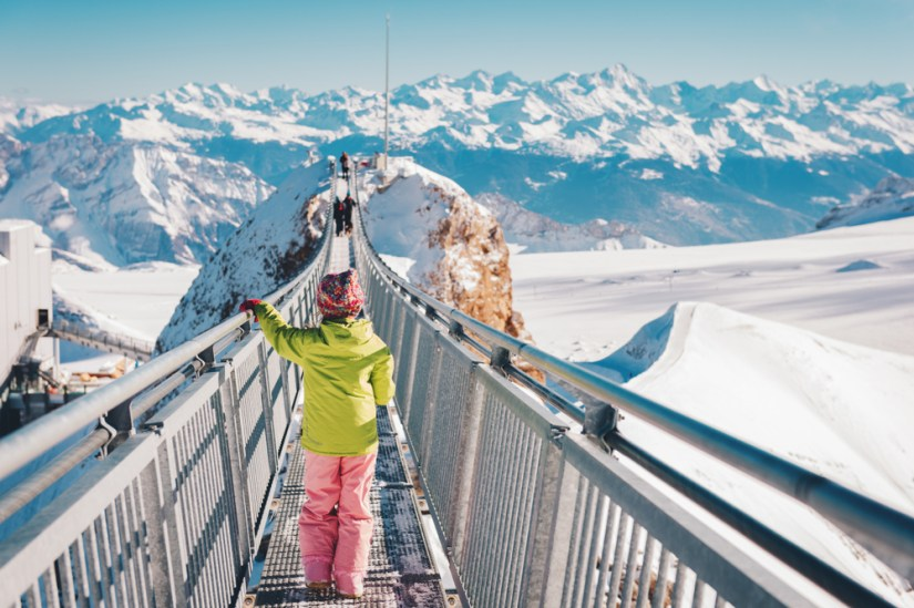 a small child in a green jacket and pink pants on a glacier walk in the swiss glaciers and mountains