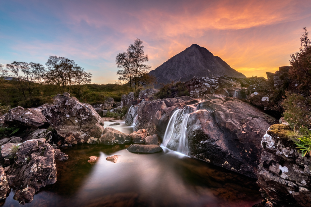 Mountain with waterfall in foreground at sunset