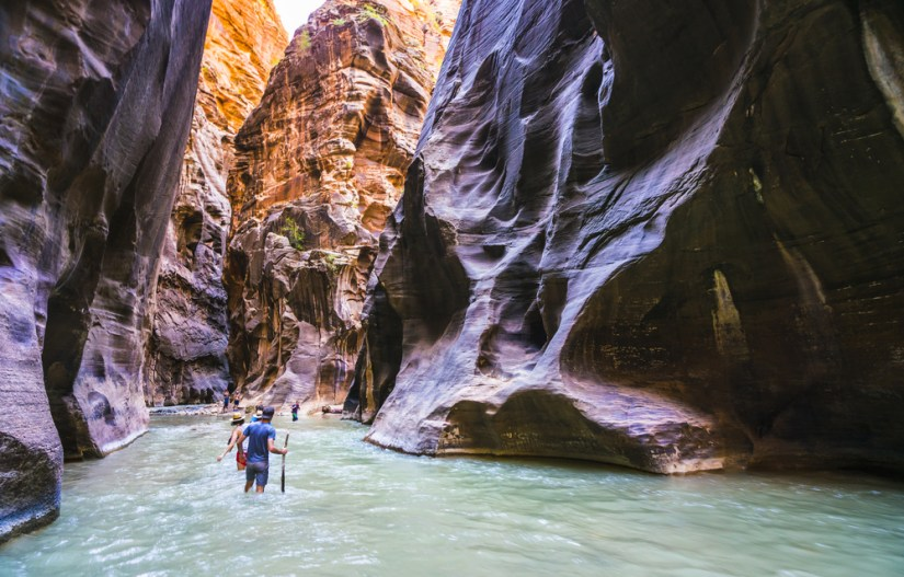 People hiking in knee-deep water in hiking sticks in a slot canyon with purplish rocks and pale green water.