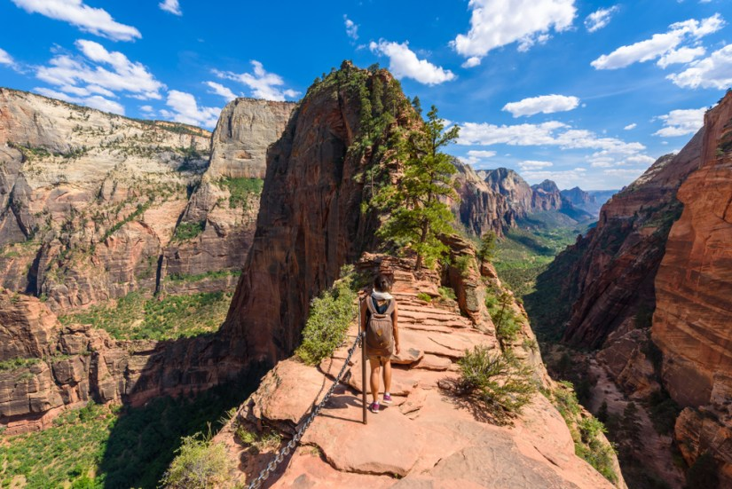 Woman hiking Angels Landing, a ridge hike with a chain assist, with views of the valley in Zion National Park on all sides.
