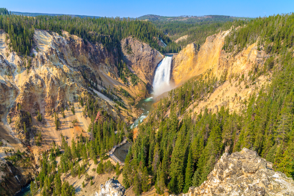 A giant waterfall in a massive canyon surrounded by trees and orange-yellow rock canyon.