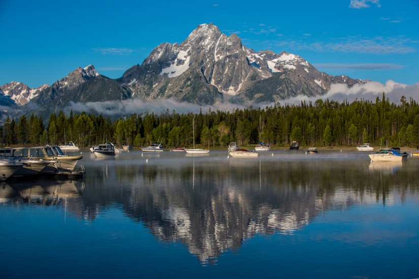 A mountain perfectly reflecting in the still water at Colter Bay, with lots of boats sitting still in the water, anchored.