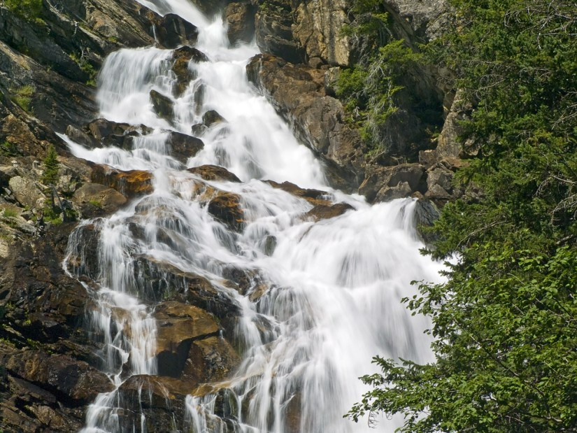 Close up of a section of a waterfall cascading down rocks with some green trees in the foreground.