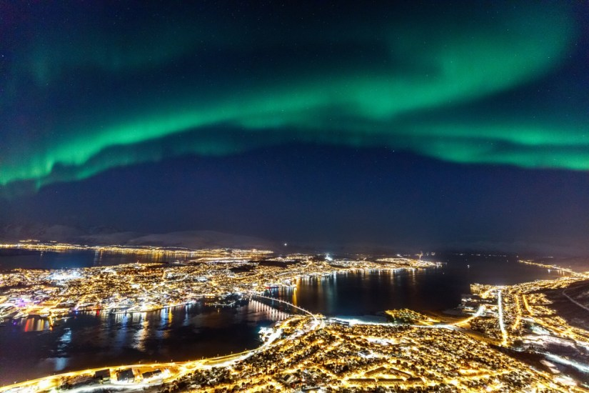 Northern lights over the city of Tromso as seen from the viewing platform at Fjellheisen cable car