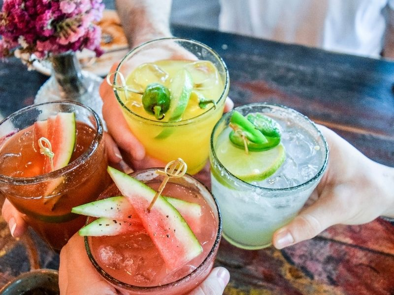 Four hands holding colorful drinks including one with watermelon and one with lime.