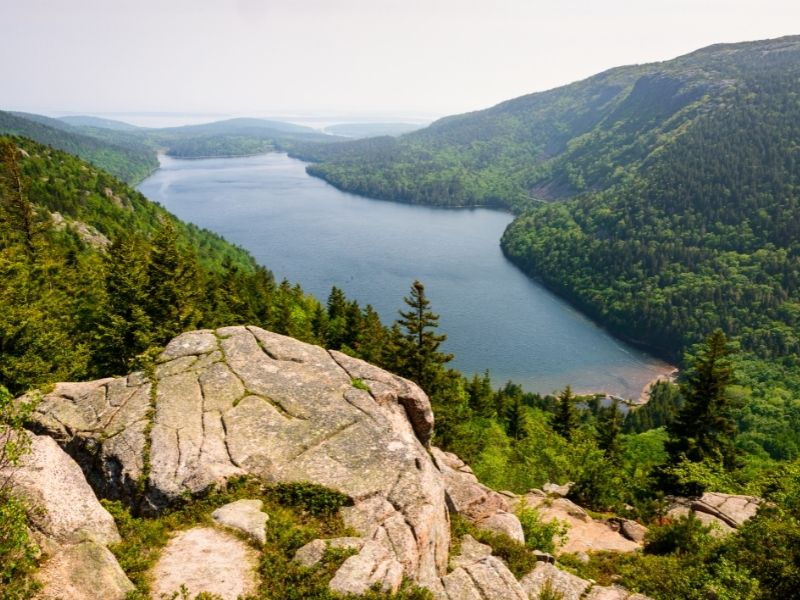 looking down on a lake in acadia national park from a rock at the top of a hiking area