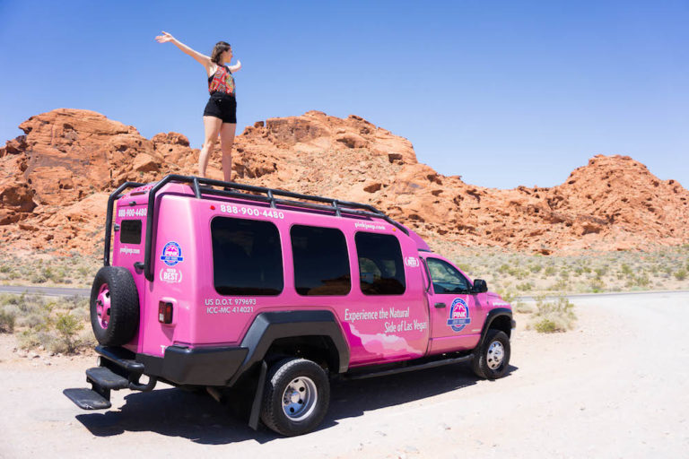 Allison standing on a pink jeep in the red rocks of Valley of Fire while on a pink jeep tour in Vegas - the same company runs tours in Sedona