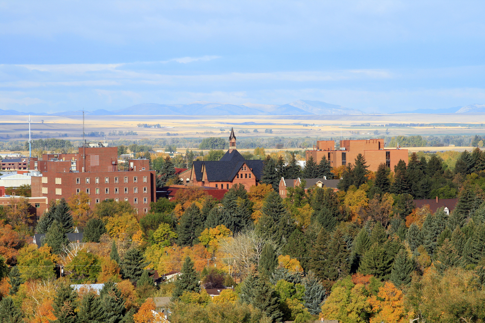 Bozeman in the early fall, orange-pink college buildings surrounded by green and orange trees.
