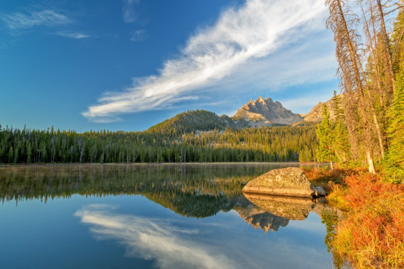 A lake with a perfect reflection on the evergreen trees and mountains in the still water, some yellow and orange fall foliage in the left corner.
