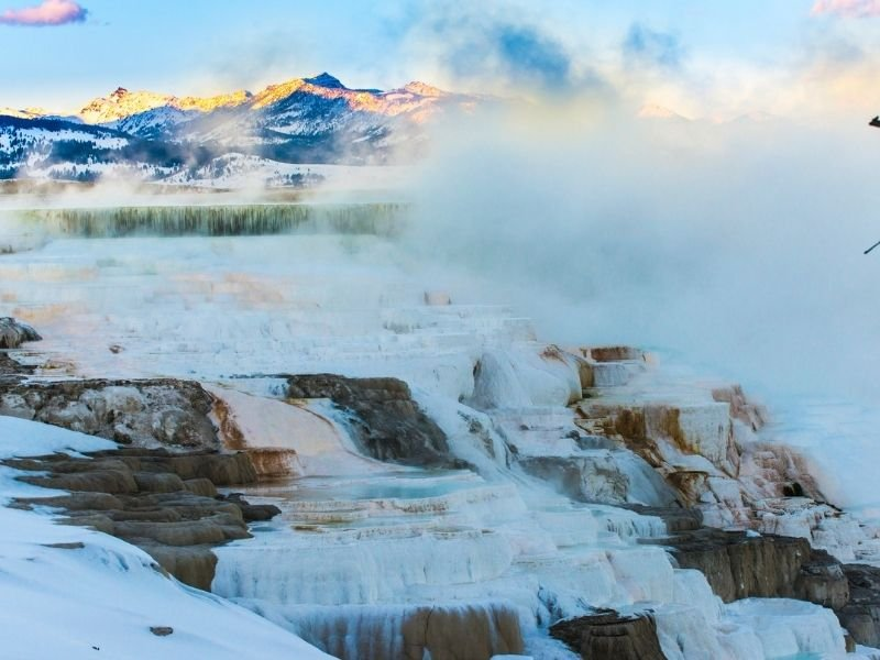 View of Mammoth Hot Springs in sunrise light with lots of mist and steam and pastel colors from morning sun.