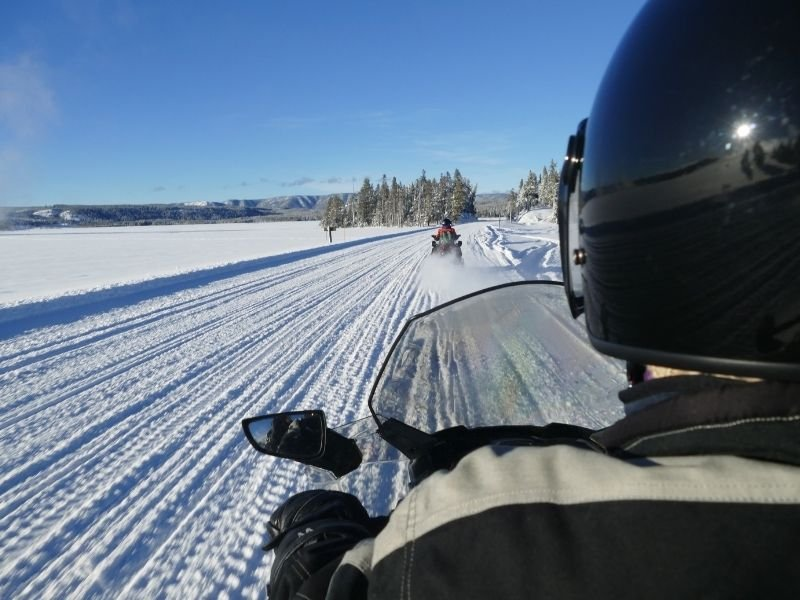 View from behind of a man on snowmobile with another snowmobile ahead on a sunny winter day.