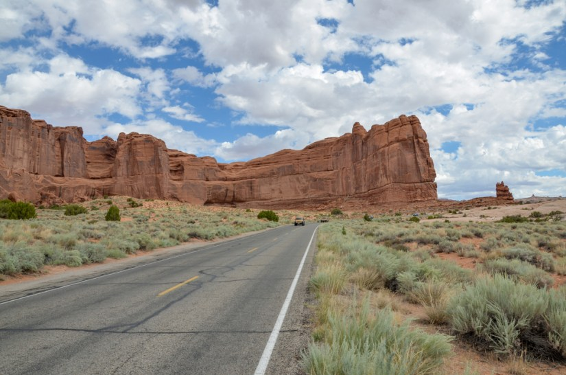 large red sandstone 'wall' next to a road with a car on it driving in arches national park on a sunny partly cloudy day.