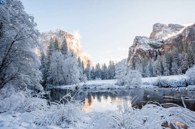 White snow covered landscape with unfrozen Merced River reflecting a snowy scenery in the background including snowy pine trees and snowy granite rock cliffs.