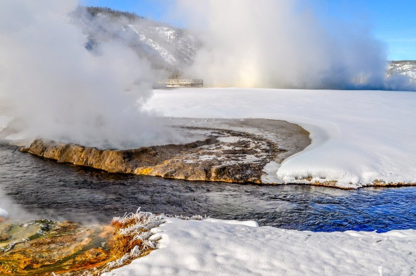 Steam rising from a geothermal feature with flowing river and snow on each side