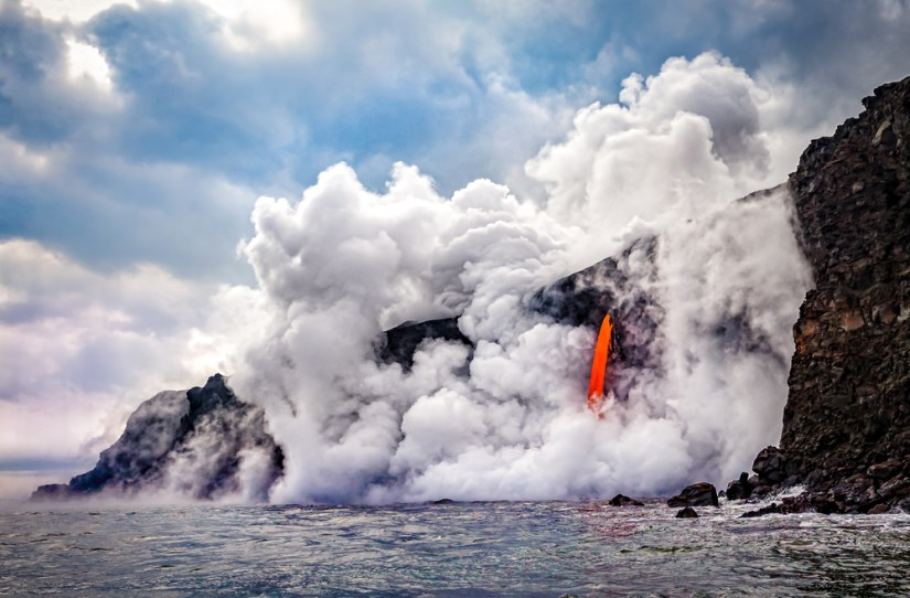 Cloudy sky with a view of orange lava flowing into the Pacific Ocean, causing a large cloud of white-gray smoke at the place where lava meets water.