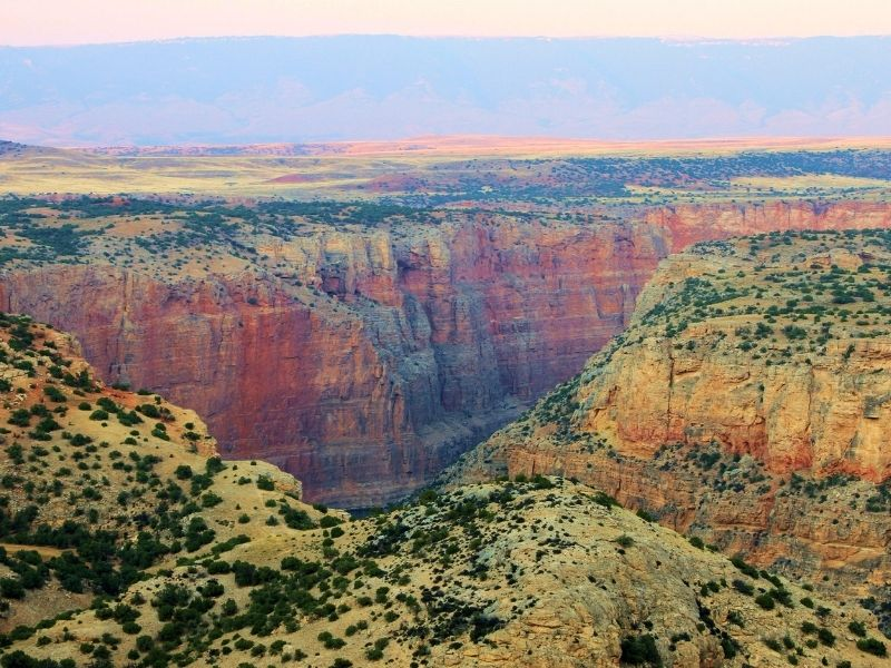 A Grand Canyon looking landscape with rocks with red, orange, and yellow tones creating a large canyon.