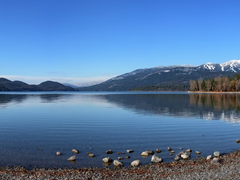 The shores of Lake Whitefish near Glacier National Park, a popular place to stay for easy park access. The lake is clear with some ripples and a slight reflection of the mountains.