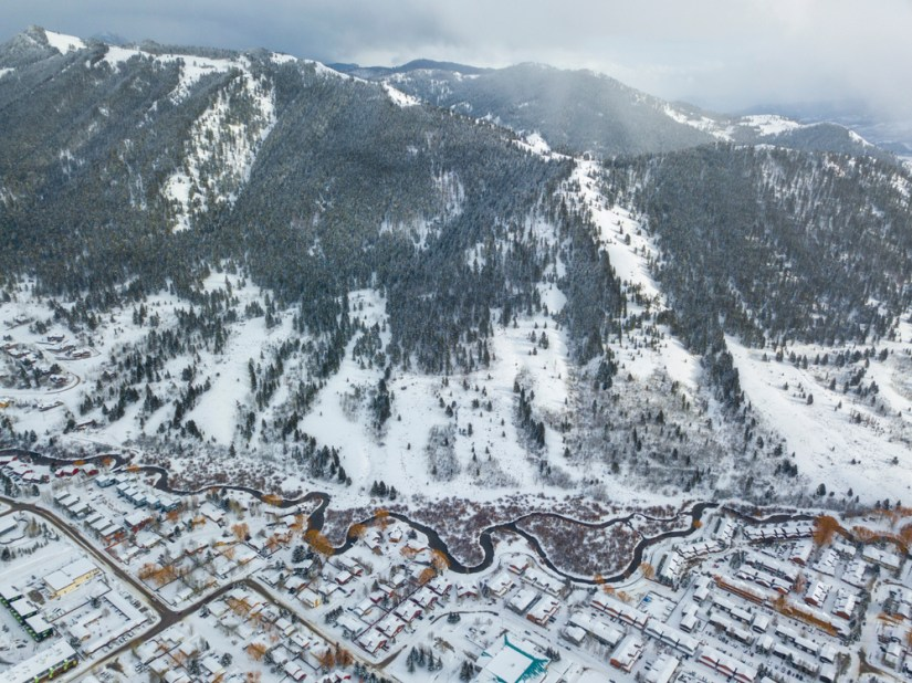 An aerial photo taken with a drone of Jackson Hole town with a river winding through it and mountains on the edge of town