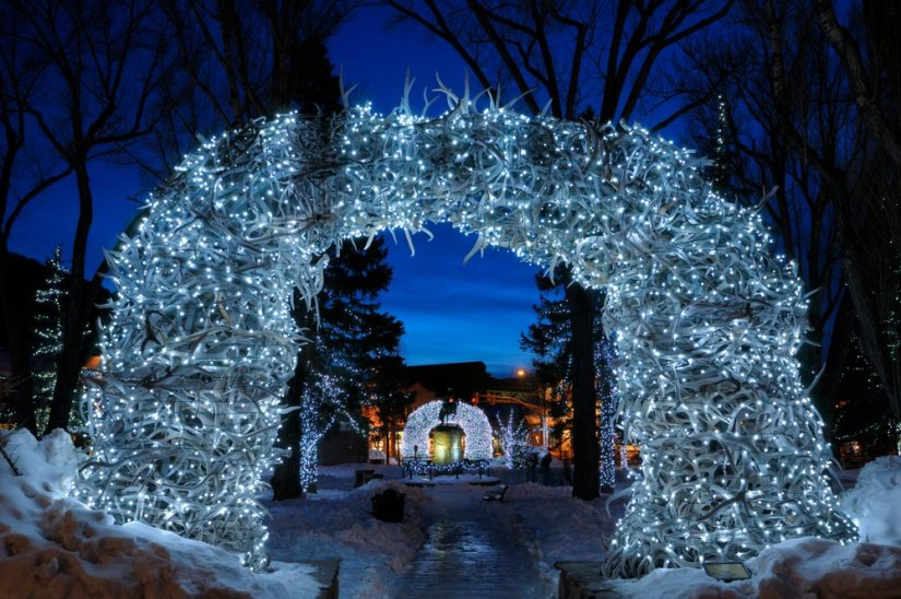 """The famous """"antler arch"""" in Jackson in winter styling with lots of blueish Christmas lights on it, making it shine a pale blue color"""